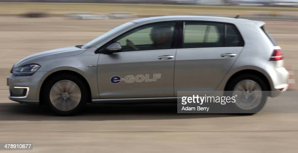 Visitor test drives a Volkswagen e-Golf automobile at the Electric Mobility Week , a public Volkswagen event at the former Tempelhof airport, on...