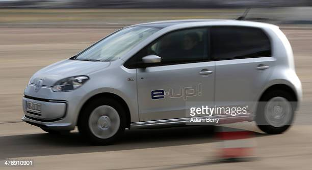 Visitor test drives a Volkswagen e-up! automobile at the Electric Mobility Week , a public Volkswagen event at the former Tempelhof airport, on March...