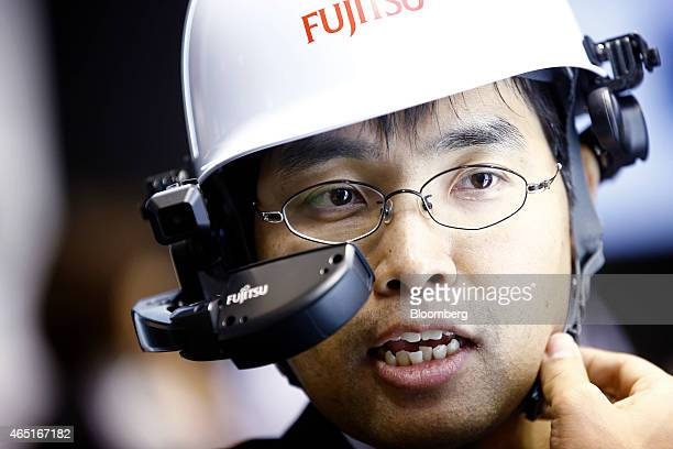 A visitor tests a digital headset device in the Fujitsu Ltd pavilion at the Mobile World Congress in Barcelona Spain on Tuesday March 3 2015 The...