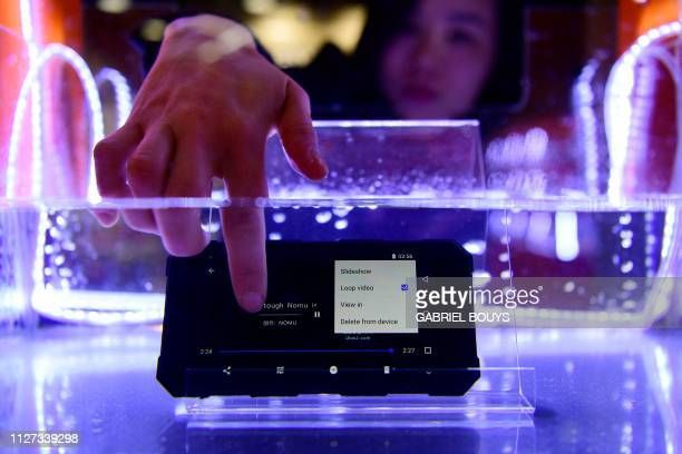TOPSHOT A visitor tests the Nomu S50 Pro waterproof smartphone at the Mobile World Congress in Barcelona on February 25 2019 Phone makers will focus...