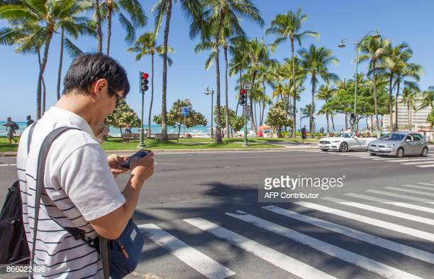 A visitor texts before crossing the street in Waikiki Tuesday October 24 2017 in Honolulu Hawaii The Honolulu Police Department will start enforcing...