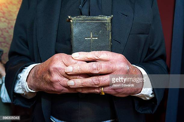 A visitor to a gold town museum dresses as a pastor to have a souvenir period drama photograph taken.