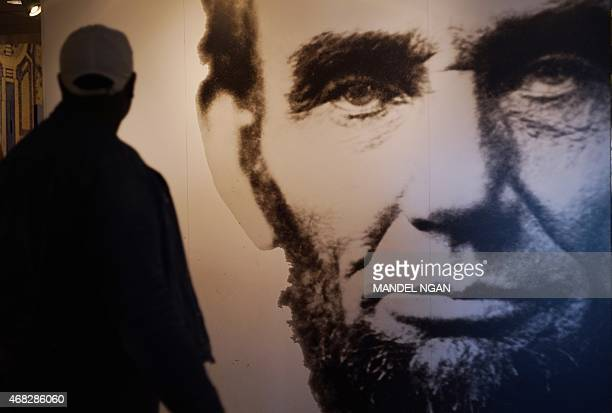 A visitor to an exhibit at the Lincoln Memorial walks past an image of Abraham Lincoln on April 1 2015 in Washington DC The nation will mark the...