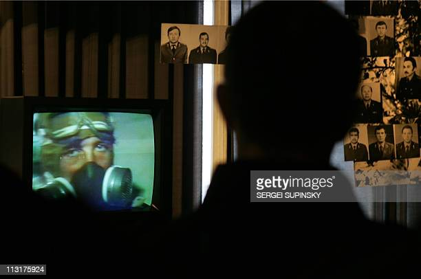 A visitor to Chernobyl's catastrophe museum in Kiev watches 18 April 2006 a documentary film about liquidators some 600000 front line soldiers...