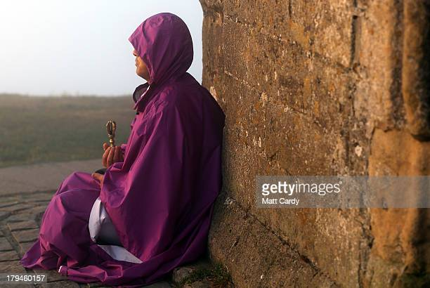 A visitor to Glastonbury Tor meditates beside St Michael's Tower a ruined 14thcentury church tower as the sun rises and begins to clear the early...