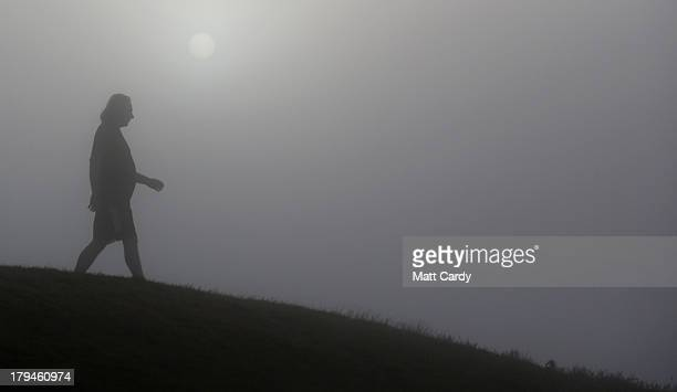 A visitor to Glastonbury Tor walks past the rising sun as it begins to clear the early morning mist and fog near the town of Glastonbury on September...