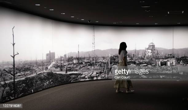A visitor to Hiroshima Peace Memorial Museum views a large scale panoramic photograph of the aftermath of the atomic bomb attack on Hiroshima on...