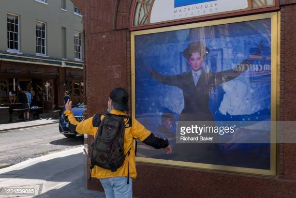 A visitor to London wearing a face mask on his chin takes a selfie of himself in front of the image of Mary Poppins outside the Prince Edward Theatre...