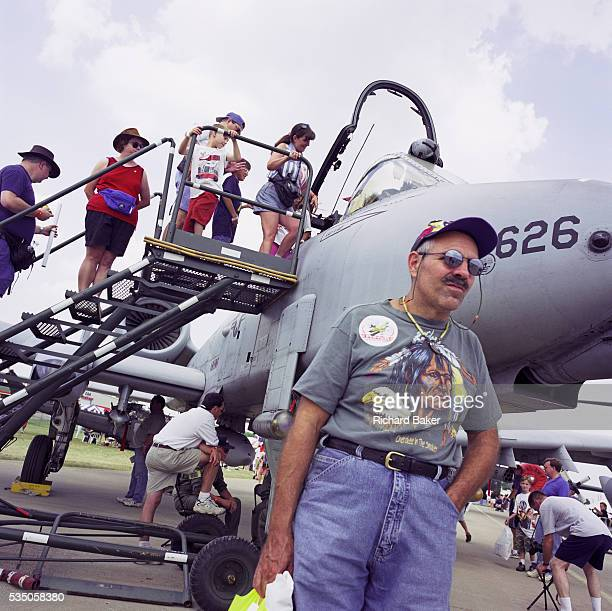 A visitor to Oshkosh Air Venture the world's largest air show in Wisconsin USA stands by an A10 Thunderbolt Tank Buster or Warthog Wearing a tshirt...