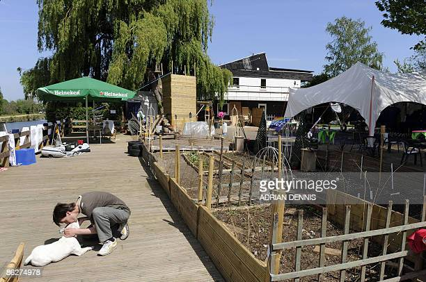 Visitor to Raven's Ait kisses a dog in the garden area of the island near Kingston-Upon Thames, west of London, on April 24, 2009. A bucolic,...