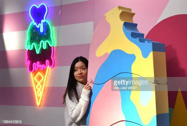 A visitor to Sugar Republic poses in front of a giant ice cream in Melbourne on July 24 2018 Sugar Republic is an interactive popup museum dedicated...