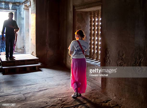 Visitor to the Angkor Wat temple poses in a lighted doorway.