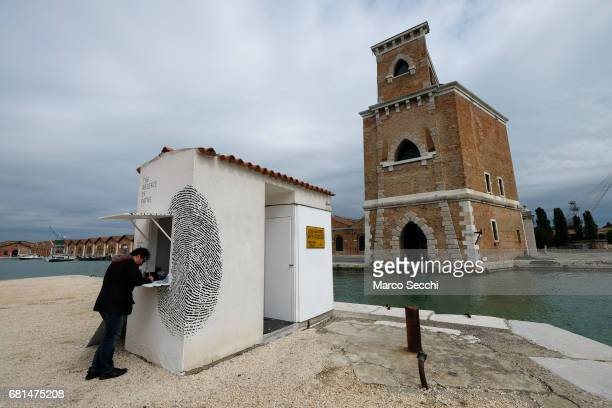 A visitor to the Biennale gets his freesa in a mock customs check point entitled #theabsenceofpaths in the Tunisian pavilion on May 10 2017 in Venice...