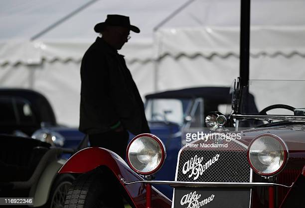 A visitor to The Brooklands Double Twelve Motorsport Festival admires a vintage Alfa Romeo car on June 18 2011 in Weybridge England Two hundred...