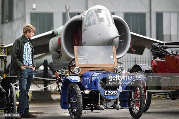 A visitor to The Brooklands Double Twelve Motorsport Festival admires a 1914 Morgan Three Wheeler in front of a Hawker P1127 prototype jet aircraft...