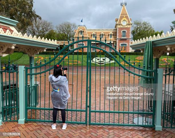 A visitor to the Disneyland Resort takes a picture through a locked gate at the entrance to Disneyland in Anaheim CA on Monday Mar 16 2020 The entire...
