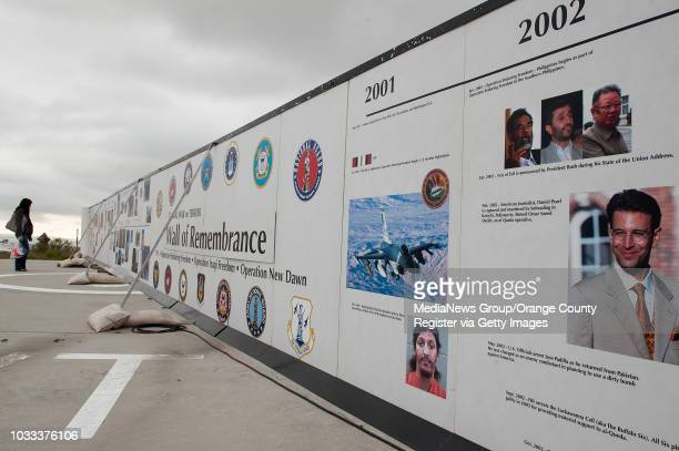 A visitor to the Global War on Terror Wall of Remembrance at Oakley headquarters in Lake Forest follows the timeline and photos on the wall...