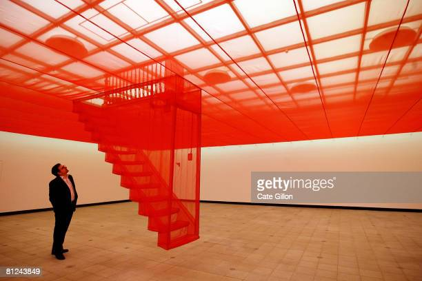 A visitor to the Hayward Gallery looks up to Doh Ho Suh's exhibit 'Staircase V 2008' made of polyester and stainless steel on May 27 2008 in London...