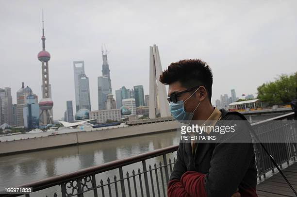 A visitor to the historic Bund district in Shanghai wears a facemask on April 19 2013 Experts from the UN's health agency arrived in China on a...
