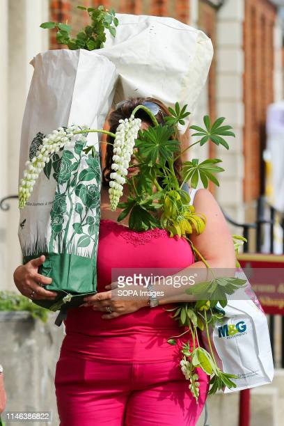 Visitor to the RHS Chelsea Flower Show seen carrying plants and flowers during the final day of the show. The Royal Horticultural Society Chelsea...