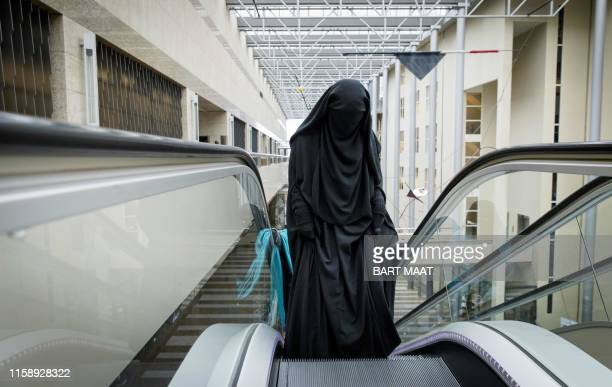 Visitor to the Second Chamber rides an escalator dressed in a niqab, prior to a debate on Islamic face covering in The Hague on November 23, 2016. -...