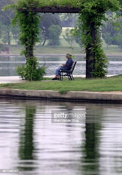 A visitor to the Sepulveda Dam Recreation Area sits under a arbor on the shore of Lake Balboa Friday afternoon on a overcast day 5 May 2000