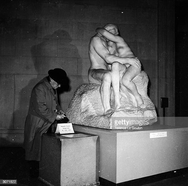 A visitor to the Tate Gallery in London places money in a collection box next to one of the three marble originals of Auguste Rodin's 'The Kiss' The...