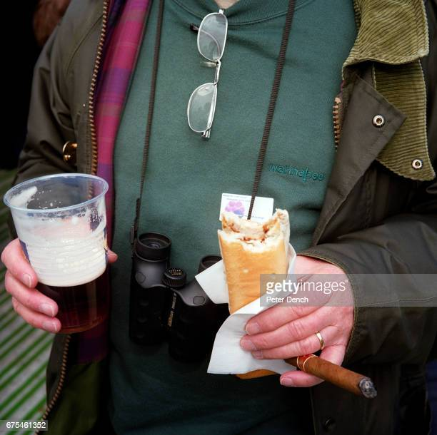 A visitor to Twickenham Stadium holds a pint of beer a hot dog and a cigar April 2001