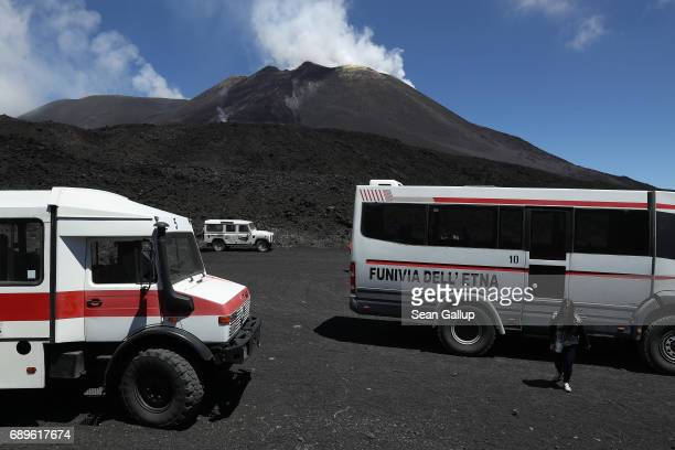 A visitor touches hot gravellike ash only about 20 centimeters below the surface while hiking among craters near the peak of Mount Etna on the island...