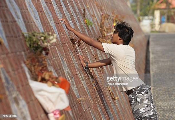 A visitor touches the wall of rememberance at the Baan Nam Kem Memorial Tsunami park January 13 2006 in Khao Lak Thailand Over a year after the...