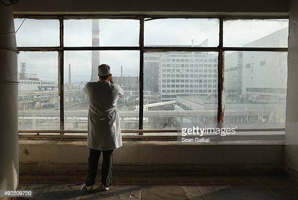 A visitor touring the former Chernobyl nuclear power plant takes a photo through a window looking towards facilities that house reactors one and two...