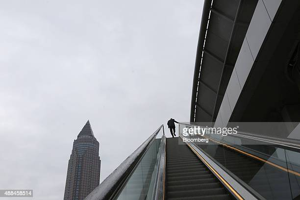 A visitor travels on an escalator as the Messeturm skyscraper stands outside the IAA Frankfurt Motor Show in Frankfurt Germany on Wednesday Sept 16...