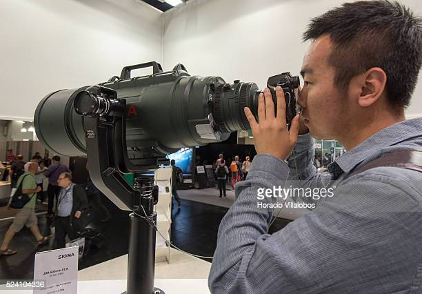 A visitor tries a 200500 mmf 28 zoom at Sigma stand in Photokina 2014 in Cologne Germany 18 September 2014 Photokina the world's leading imaging fair...