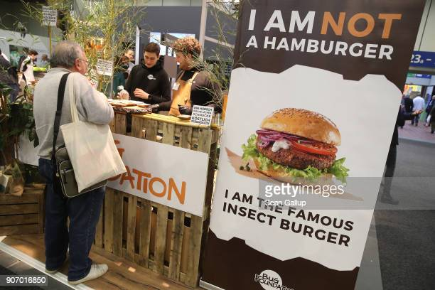 A visitor tries meat patties made from ground buffalo worms at the 2018 International Green Week agricultural trade fair on January 19 2018 in Berlin...