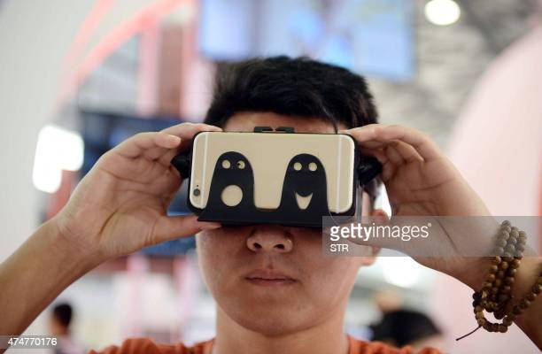 A visitor tries on a device which can transform movies played on mobile phones into 3D movies during the first Consumer Electronics Show in Asia in...