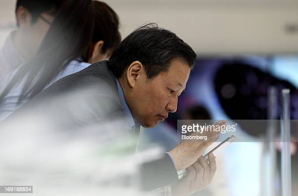 Visitor tries out a Samsung Electronics Co. Galaxy S4 smartphone at the World IT Show 2013 in Seoul, South Korea, on Tuesday, May 21, 2013. The IT...