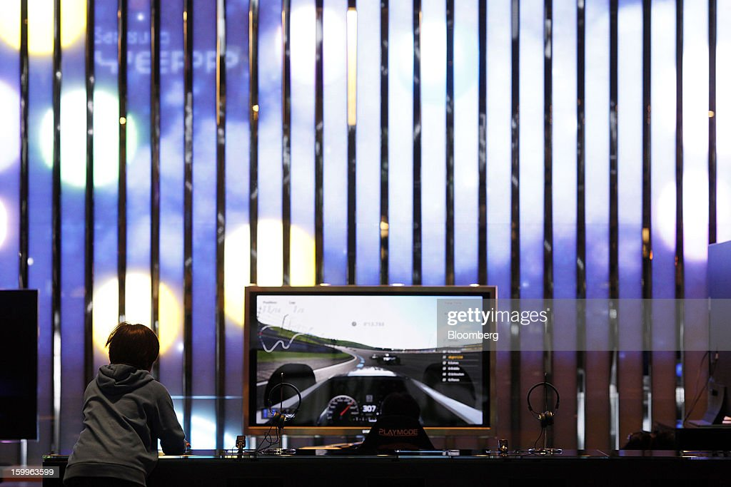 A visitor tries out a Samsung Electronics Co. LED TV at the Samsung d'light showroom and store in Seoul, South Korea, on Wednesday, Jan. 23, 2013. Samsung, in a preliminary statement of results on Jan. 8, reported an 89 percent jump in profit in the three months ended in December, boosted by its Galaxy line of smartphones. Photographer: Woohae Cho/Bloomberg via Getty Images