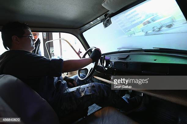 A visitor tries out a video game experience inside a Trabant the iconic car of the former communist East Germany at the DDR Museum on October 8 2014...