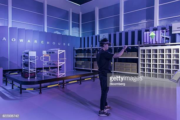 A visitor tries out a virtual reality logistics system in a booth for Cainiao Smart Logistics Network Ltd Alibaba Group Holding Ltd's delivery...