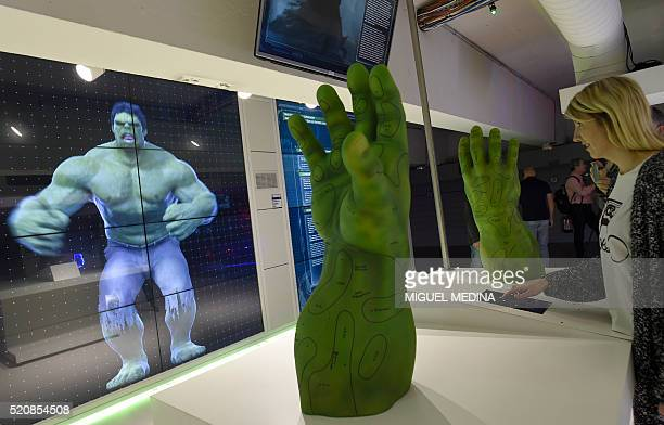 A visitor tries out an interactive display on Marvel Comics superhero The Hulk at the interactive Marvel Avengers STATION exhibition in the bussines...