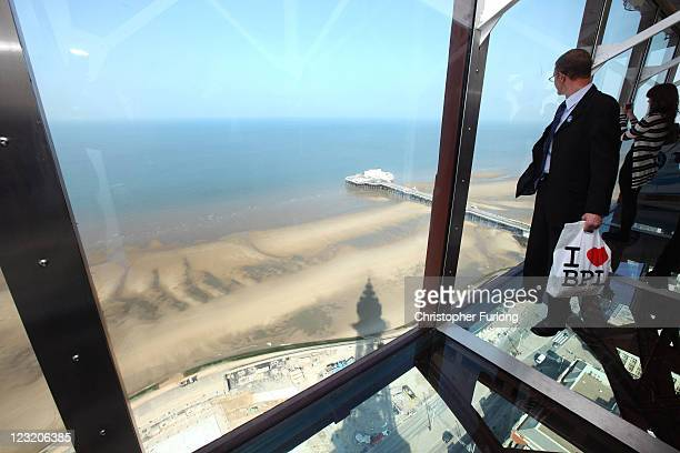 A visitor tries out the new glass Skywalk at the top of the refurbished Blackpool Tower on September 1 2011 in Blackpool England After a 20million...
