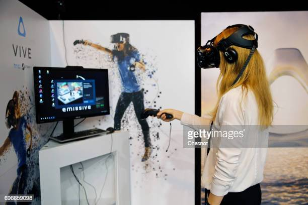 A visitor tries the virtual reality headset 'HTC vive' to experience 3D virtual reality during the Viva Technology show on June 16 2017 in Paris...