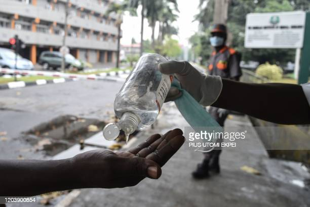 Visitor tries to sanitise hands before being allowed into a state hospital at Yaba in Lagos, on February 28, 2020. - Residents of Nigeria's economic...