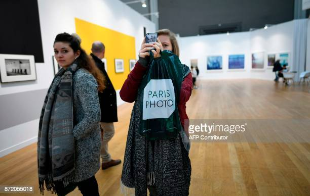 A visitor uses a cellular telephone as she attends 'Paris Photo' at The Grand Palais in Paris on November 9 2017 / AFP PHOTO / Lionel BONAVENTURE