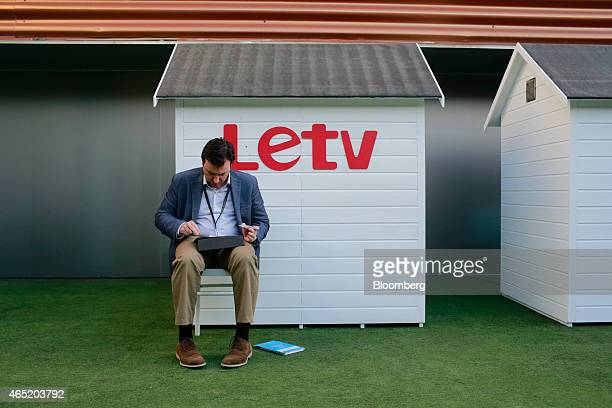 A visitor uses a laptop computer in a networking garden beside a LeTV logo at the Mobile World Congress in Barcelona Spain on Tuesday March 3 2015...
