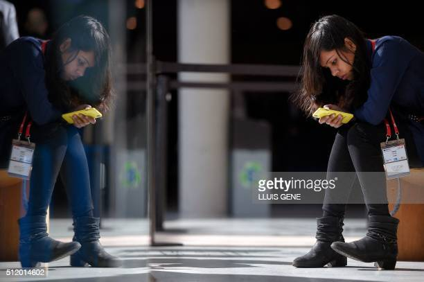 A visitor uses a mobile phone on the third day of the Mobile World Congress in Barcelona on February 24 2016 The world's biggest mobile fair Nobile...