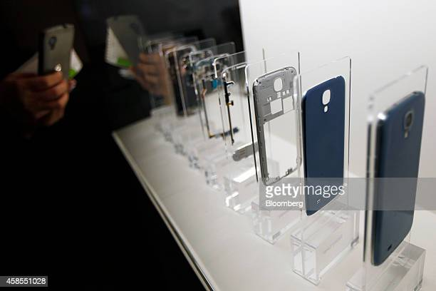 A visitor uses a mobile phone to photograph a disassembled Samsung Galaxy S4 smartphone on display in an exhibition hall at the Samsung Innovation...
