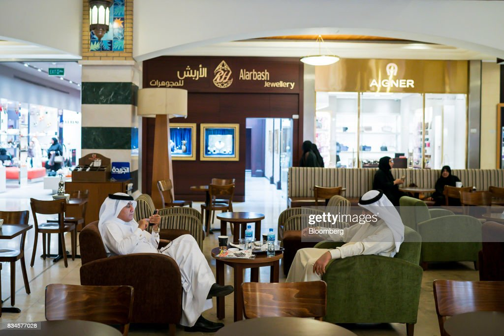 A visitor uses a mobile phone while sitting in a coffee shop terrace at the Souq Sharq shopping mall in Kuwait City, Kuwait, on Monday, Aug. 14, 2017. Kuwait will issue a tender to build the estimated $1.2 billion Dibdibah solar-power plant in the first quarter of 2018 as part of the countrys plans to produce 15 percent of power from renewable energy by 2030. Photographer: Tasneem Alsultan/Bloomberg via Getty Images