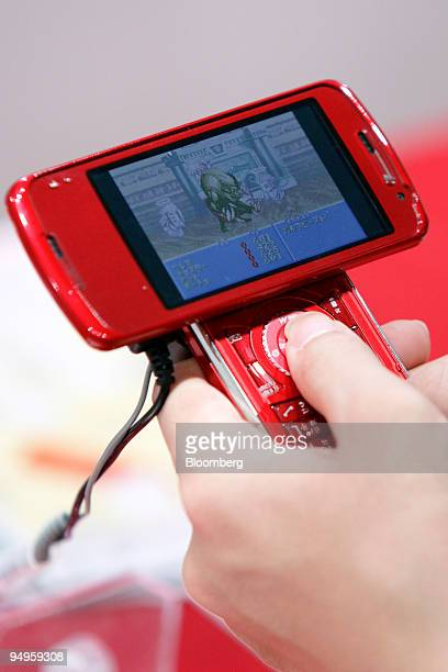 A visitor uses a NTT DoCoMo Inc's mobile phone to play a video game during a media preview at the Tokyo Game Show 2009 in Chiba City Japan on...