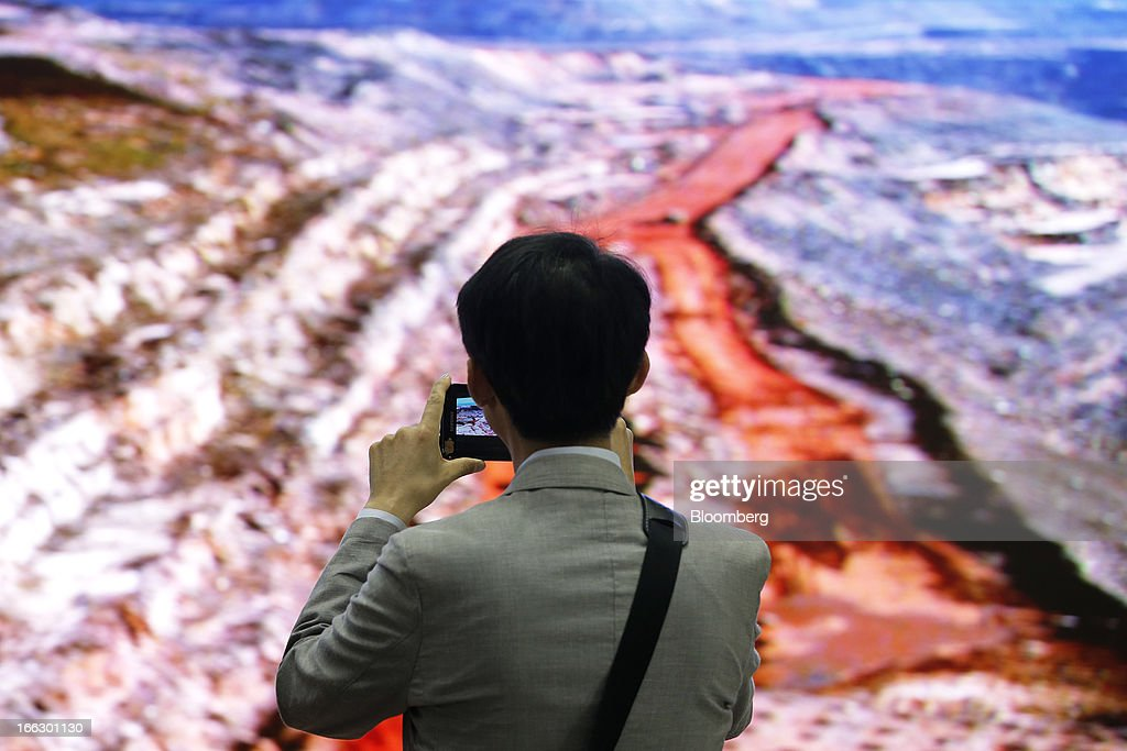 A visitor uses a Samsung Electronics Co. device to take a photograph of SiliconSign Inc.'s 1.9mm super fine pitch light-emitting diode (LED) panel display at the company's booth at the Finetech Japan exhibition in Tokyo, Japan, on Thursday, April 11, 2013. Finetech Japan, the world's largest flat panel display exhibition, will be held through April 12. Photographer: Kiyoshi Ota/Bloomberg via Getty Images